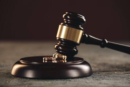 Eheringe auf der Figur eines gebrochenen Herzens von einem Baum, Hammer eines Richters auf einem hölzernen Hintergrund. Scheidungsverfahren.