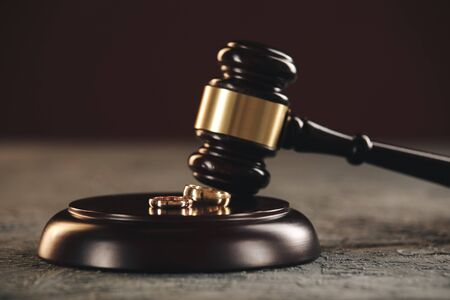 Trouwringen op de figuur van een gebroken hart van een boom, hamer van een rechter op een houten achtergrond. echtscheidingsprocedure.