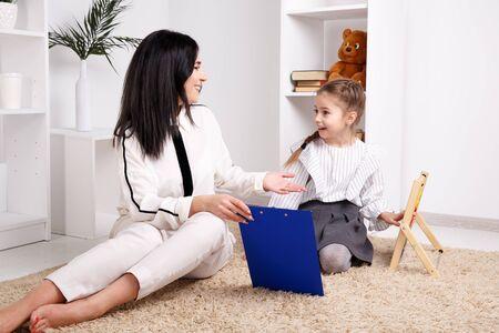 Vrouw met kind meisje opleiding toespraak samen zitten in de witte kamer.
