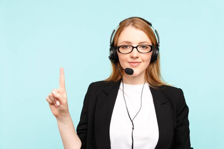 Happy female call center operator in the blue studio pointing something.