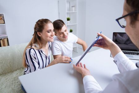 Professional trader showing contract to the couple. Mortgage concept.