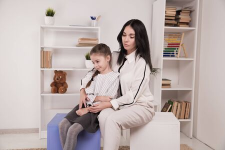 Female psychologist counseling little girl in the cabinet.