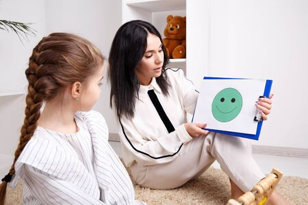 Therapist showing to the little patient smiling face on the paper. Psychologist consept.