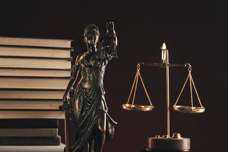 Attorney and notary concept. Books standing behind statue of justice.