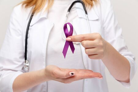 Lymphoma concept. Purple ribbon in the hand isolated.