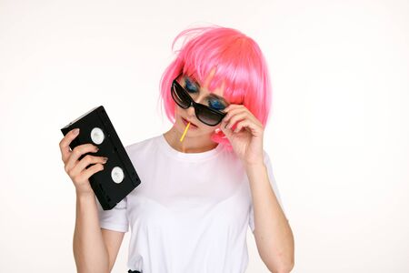 Retro girl in the glasses and pink wig holding black cassette on the white background.