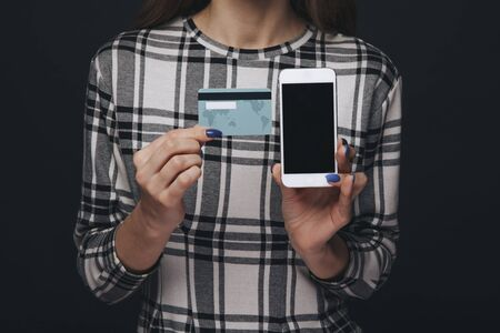 Closeup view of cellphone and credit plastic card in womans hands.