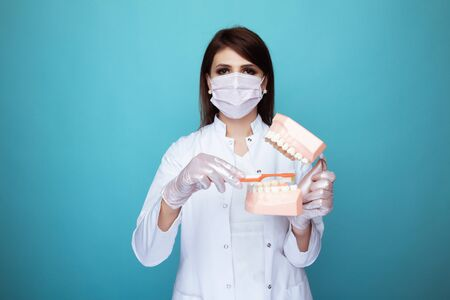Woman dentist in the white mask with dental stuff isolatedin the blue studio.