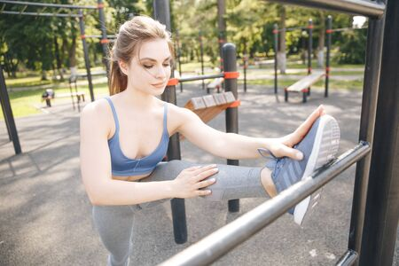 Summer outdoor training. Sporty woman doing gym in the park. Stock Photo