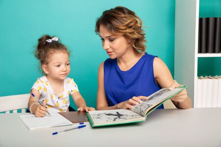 Mother and kid spending time together by sitting and learning.