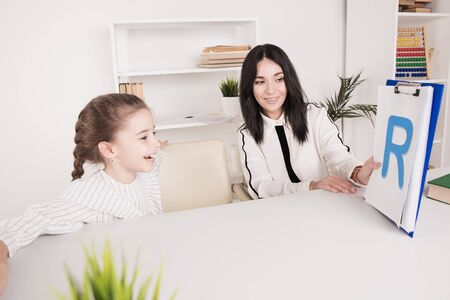 Female therapist working with kid with problem in pronunciation in the white cabinet.