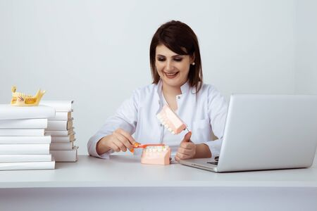 Dentist woman working sitting in office isolated with dental staff.