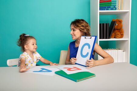 Child with therapist working on pronunciation and sounds together sitting in the class.