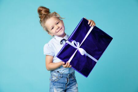 Little girl with big blue present in the box with white ribbon. New Year gift concet. Banco de Imagens