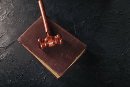 Judge gavel and legal book on wooden table, justice and law concept.