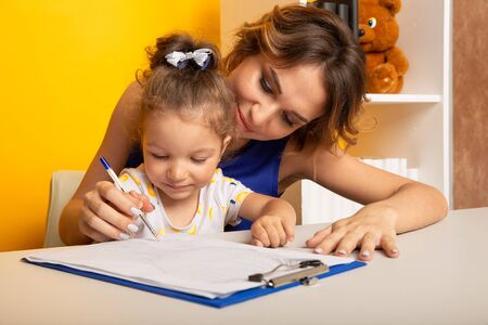 Mother and daughter sitting at the desk doing homework together.