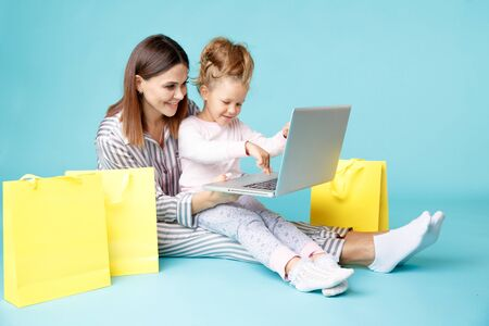 Portrait of mother and daughter with laptop sitting on the floor isolated over the blue studio. Online family shopping concept. Stok Fotoğraf