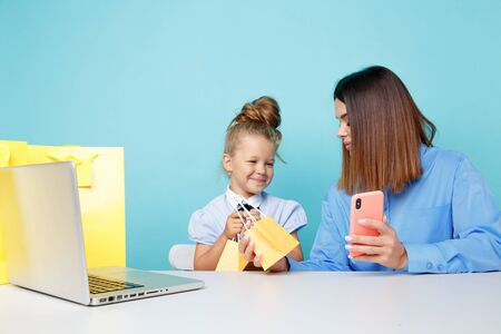 Portrait of mother and daughter with phone sitting at the table isolated over the blue studio. Online family shopping concept.