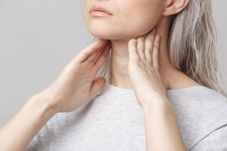 Female checking thyroid gland by herself. Close up of woman in white t- shirt touching neck with red spot. Thyroid disorder includes goiter, hypothyroid, tumor or cancer. Health care.