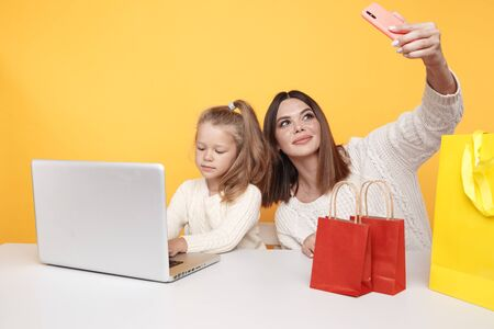 Pretty mother and cute daughter making selfie together in the yellow studio. Stock Photo