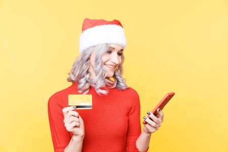 Xmas shopping online concept. Christmas girl holding credit card and phone.