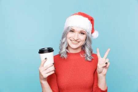 Girl in the santas hat with a cup of coffee. Archivio Fotografico - 133480418