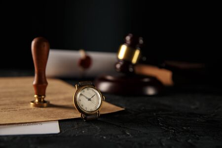 Notary stamp and wooden gavel with watch on the table Stock Photo