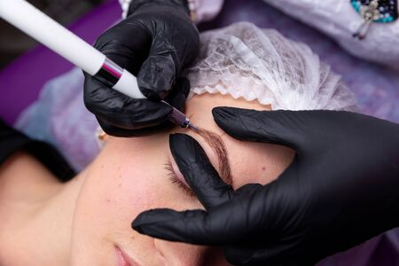 Cosmetic procedures for the treatment of eyebrows. Microblading in the beauty salon. Professional cosmetology. The process of applying the pigment
