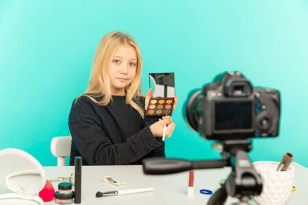 Happy girl at home speaking in front of camera for vlog. Young black woman working as blogger, recording video tutorial for Internet. Stock Photo
