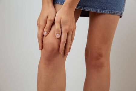 Rheumatism concept. Young lady holding her knee and feeling pain isolated. Standard-Bild