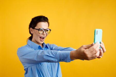 Cool handsome businesswoman posing on phones camera in the studio.