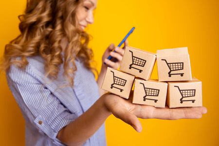 Shopping online. Woman holding paper boxes and using phone