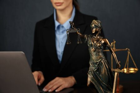 Lawyer office. Statue of Justice with scales and lawyer working on a laptop. Legal law, advice and justice concept.