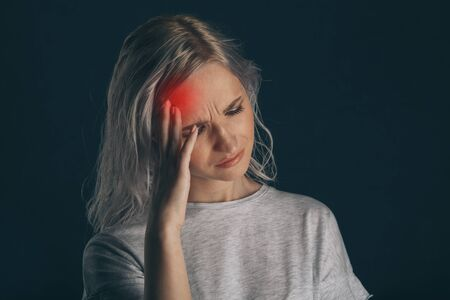 Woman in stress with pain on her face feeling headache. Stockfoto