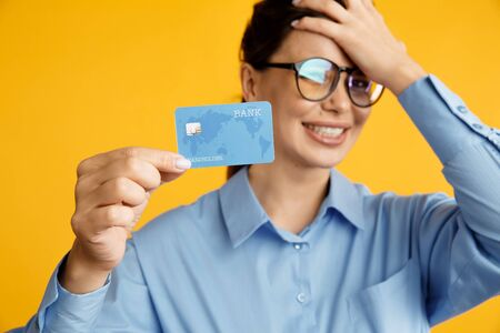 Tired of sale. Lady in glasses holding credit card and put her hand on her head. No money on card.