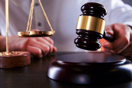 Juez de sexo masculino golpeó el mazo de madera en el escritorio. Concepto de abogado.