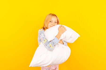 Adorable little girl looking at the camera and hugging a pillow background of a yellow wall