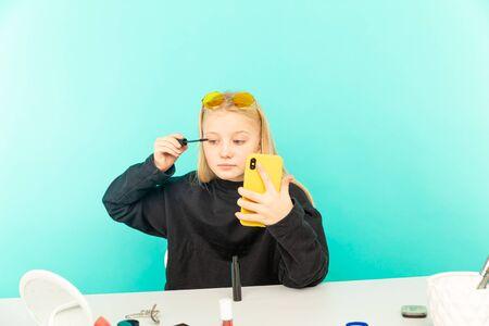 Girl beauty blogger making vlog isolated over the blue studio.