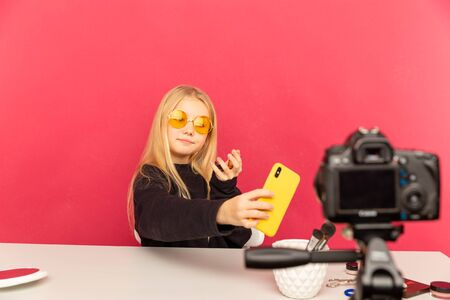 Happy girl at home speaking in front of camera for vlog. Teenager working as blogger, recording video tutorial for Internet. Stock Photo