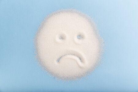 Cara de azúcar triste sobre fondo azul. Concepto de mala comida. Foto de archivo
