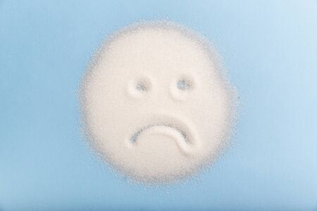 Sad sugar face on the blue background. Bad food concept. Stock Photo