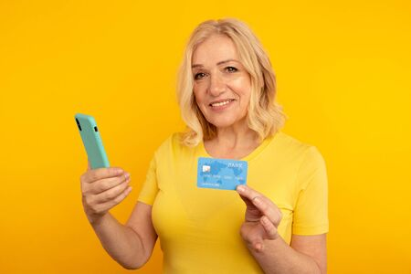 Pretty adult lady in bright clothes watching camera and posing with blue phone and credit card.