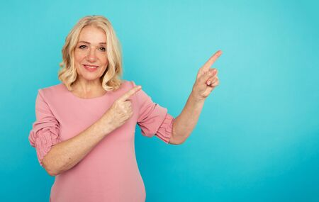 Portrait of cheerful adult woman pointing something in the blue background.