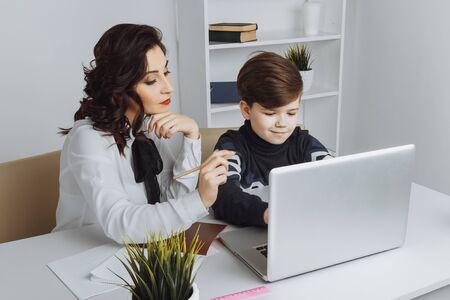 Young teacher with kid doing homework on a computer. Tutor help.