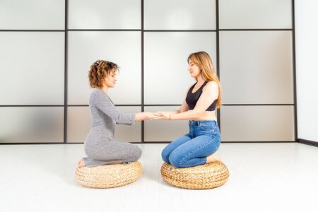 Wellness healthy concept. Meditation of two women on the floor. Relax and zen in the white room. Body care.