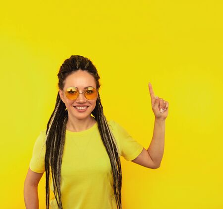 Handsome female in orange glasses pointing up standing isolated over the yellow background. Stockfoto