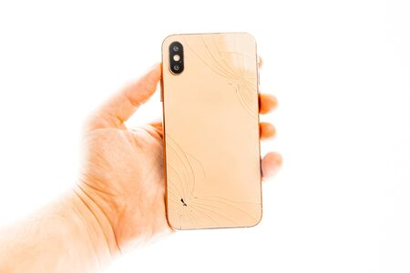 Man holding broken phone on the white background isolated.
