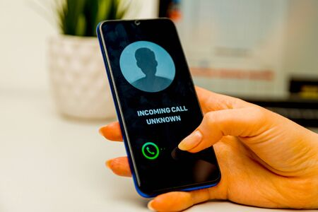 Unknown caller. A man holds a phone in his hand and thinks to end the call. Incoming from an unknown number. Incognito Stock Photo
