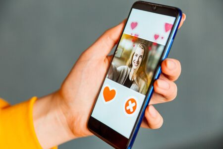 Online dating app in smartphone. Man looking at photo of beautiful woman. Person swiping and liking profiles on relationship site or application. Single guy searching for love partner. Mockup website.