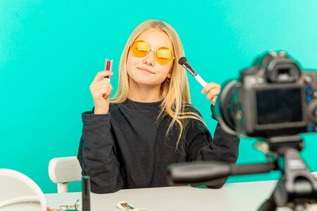 Girl beauty blogger. Blond teen posing on camera and making vlog. 스톡 콘텐츠